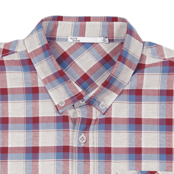 Flat lay zoomed in on the collar and top buttons of a plaid, button up shirt. Can see the Tact & Stone neck label.