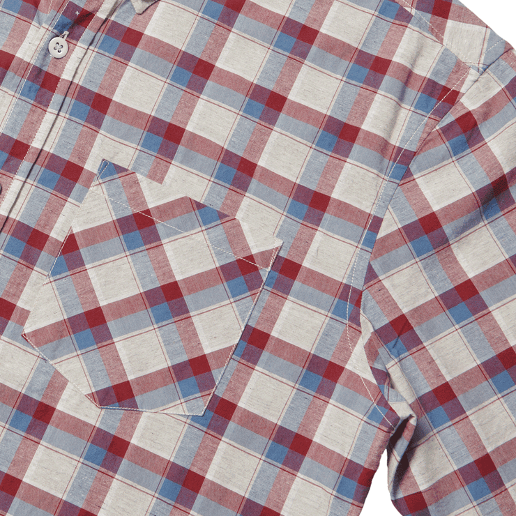 Flat lay zoomed in on left chest pocket of a plaid, button up shirt.