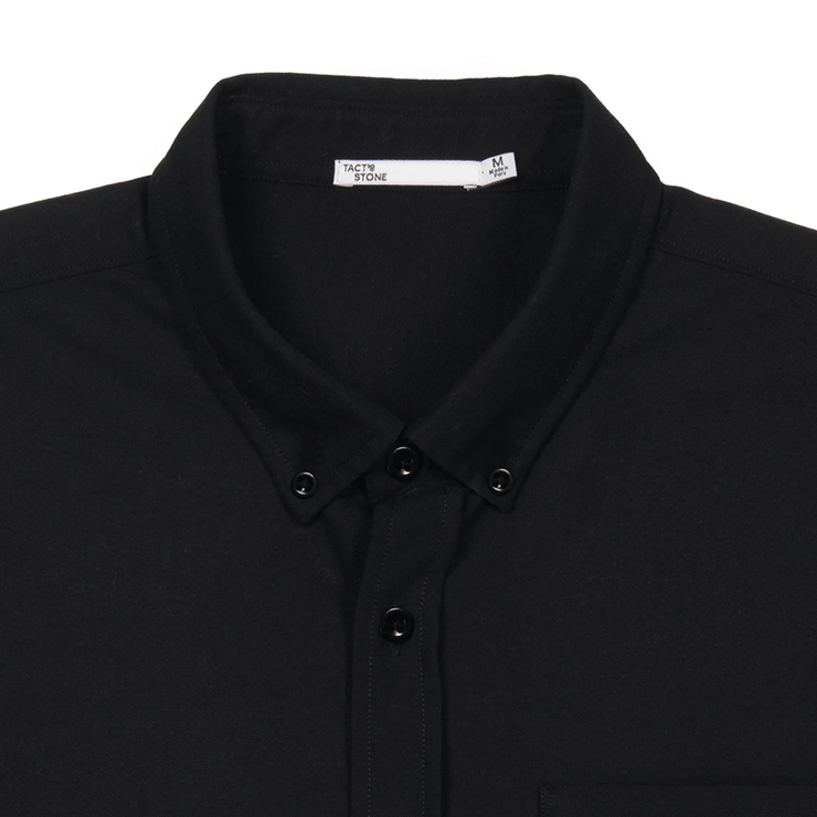 Flat lay focused on the collar of a black oxford shirt.