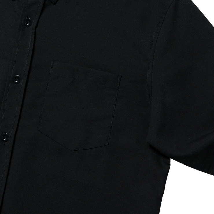 Flat lay focused on the left chest pocket of a black oxford shirt.
