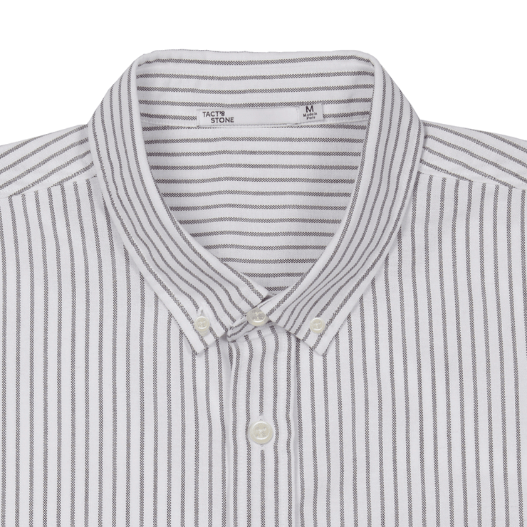Flat lay focused on the collar of a striped oxford shirt. The Tact & Stone neck label is visable.