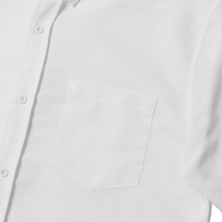 Flat lay focused on the left chest pocket of a white oxford shirt.