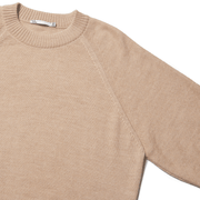 Flat lay zoomed in on raglan sleeve detail of a natural colored alpaca sweater.