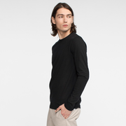 Model side facing wearing a long sleeve, black tee shirt.