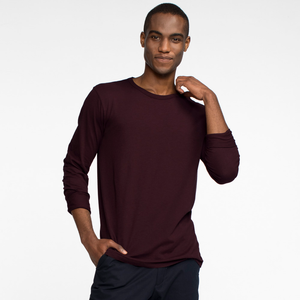 Model facing front playing with the collar of a long sleeve, burgundy tee shirt.