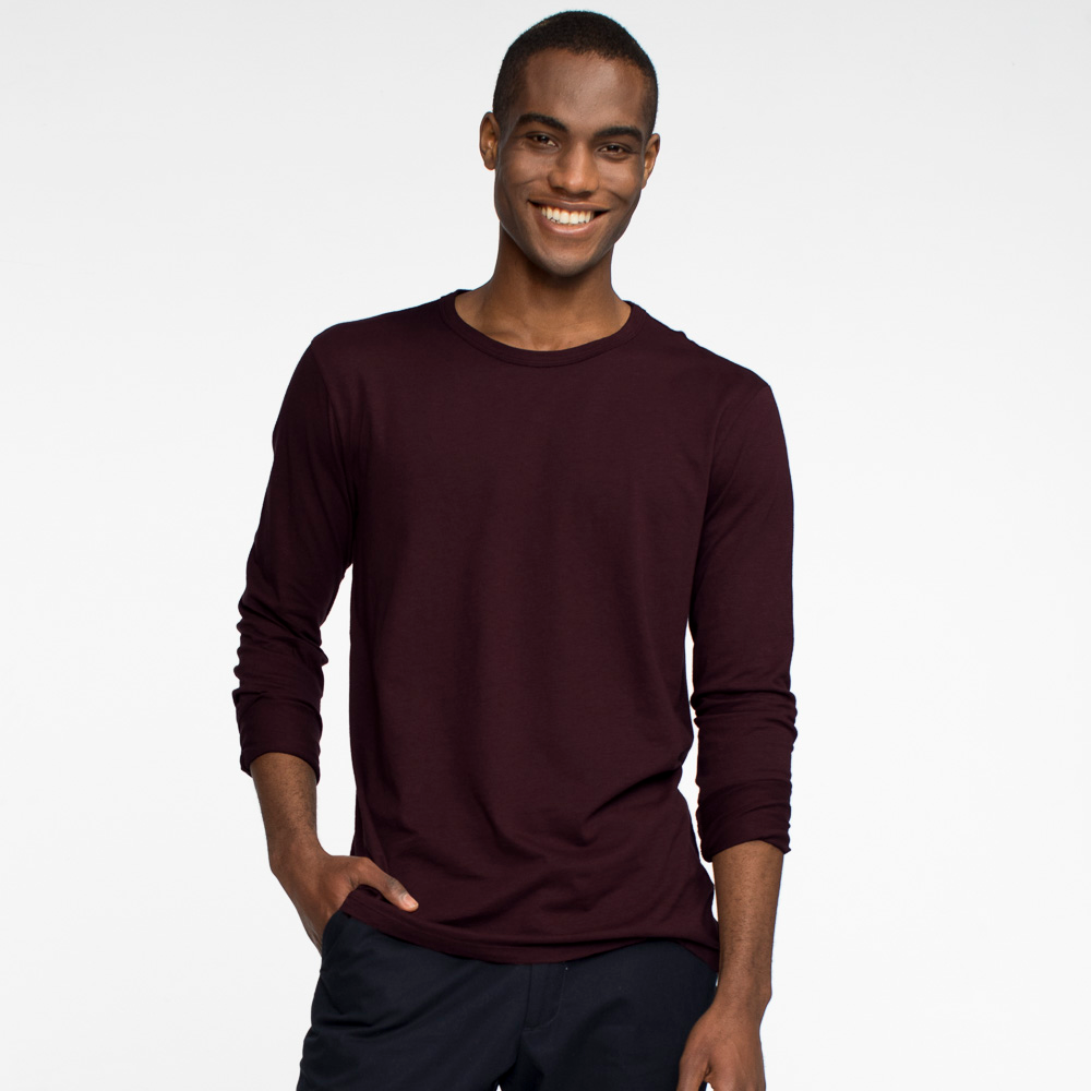 Model facing front wearing a long sleeve, burgundy tee shirt.