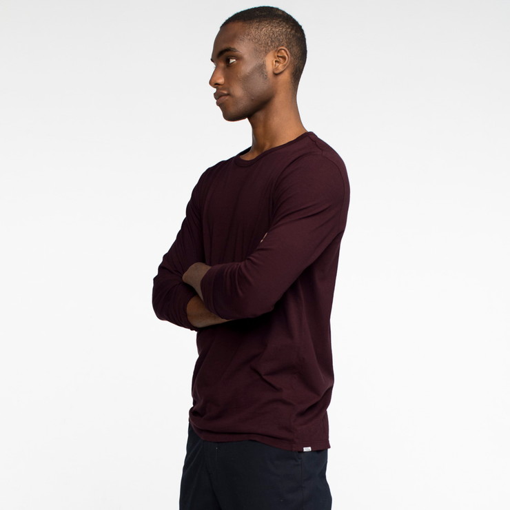 Model side facing wearing a long sleeve, burgundy tee shirt.