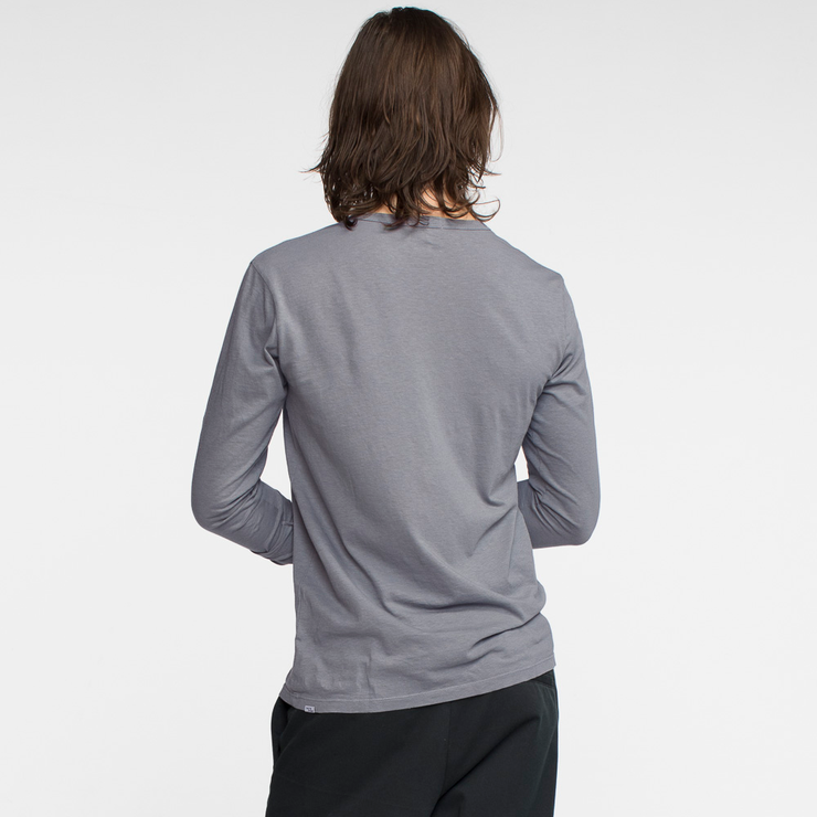 Model facing back wearing a long sleeve, slate, tee shirt.