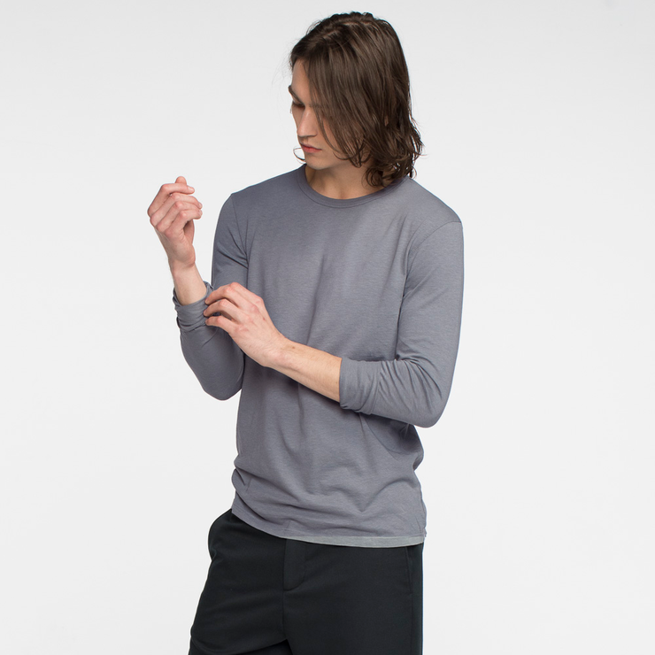 Model side facing, adjusting his sleeve, of a long sleeve, slate, tee shirt.