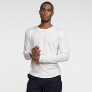 Model front facing wearing a long sleeve white tee shirt.