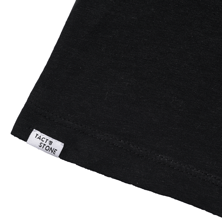 Flat lay focused on the back hem of a black tee shirt highlighting the Tact & Stone label.