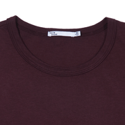 Flat lay focused on the collar of a burgundy tee shirt. You can see the Tact & Stone neck label.