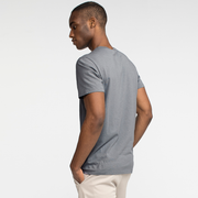 Model side facing wearing a slate, short sleeve tee shirt.