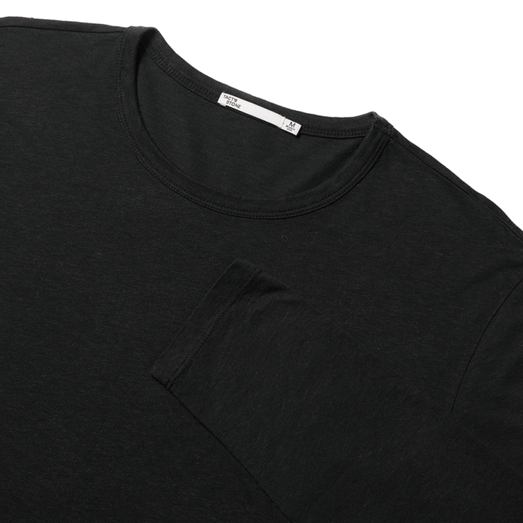 Flat lay focused on the top half of a black, long sleeved tee shirt with the sleeve folded over the chest.