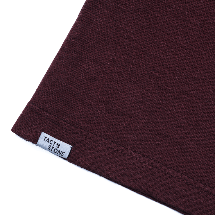 Flat lay focused on the back hem of a burgundy tee shirt highlighting the Tact & Stone label.