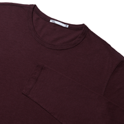 Flat lay focused on the top half of a burgundy, long sleeved tee shirt with the sleeve folded over the chest.