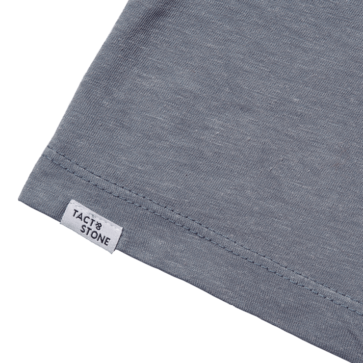 Flat lay focused on the back hem of a slate tee shirt, highlighting the Tact & Stone label.