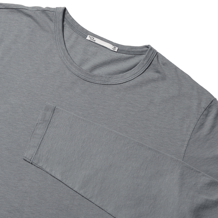 Flat lay focused on the upper half of a long sleeve, slate tee shirt, with the sleeve folded over the chest.