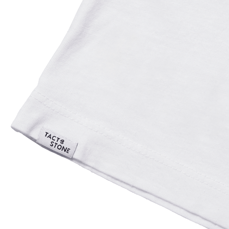 Zoomed in flat lay of the back hem of a white tee shirt focusing on the Tact & Stone label.