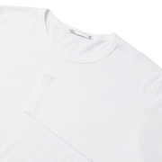 Flat lay focused on top half of a white long sleeve tee shirt, with the sleeve folded over the chest.