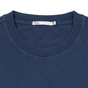 Flat lay focused on the collar of a navy tee shirt. Neck label of Tact & Stone visible.