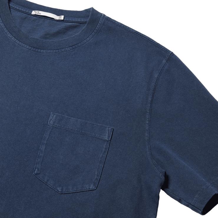 Flat lay focused on the left chest pocket of a navy, short sleeve, tee shirt.