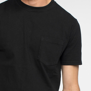 Zoomed in view of the front of a short sleeve, black, pocket tee shirt on a model.