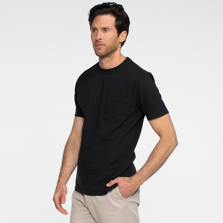 Model side facing wearing a short sleeve, black, pocket tee shirt.