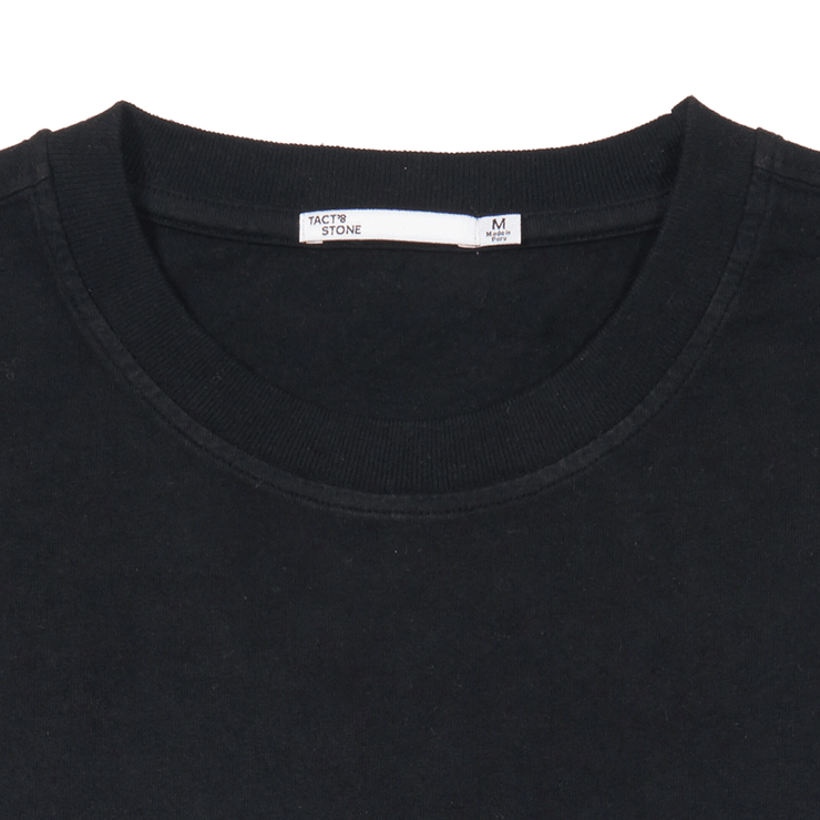 Flat lay focused on the collar and Tact & Stone neck label or a black tee shirt.