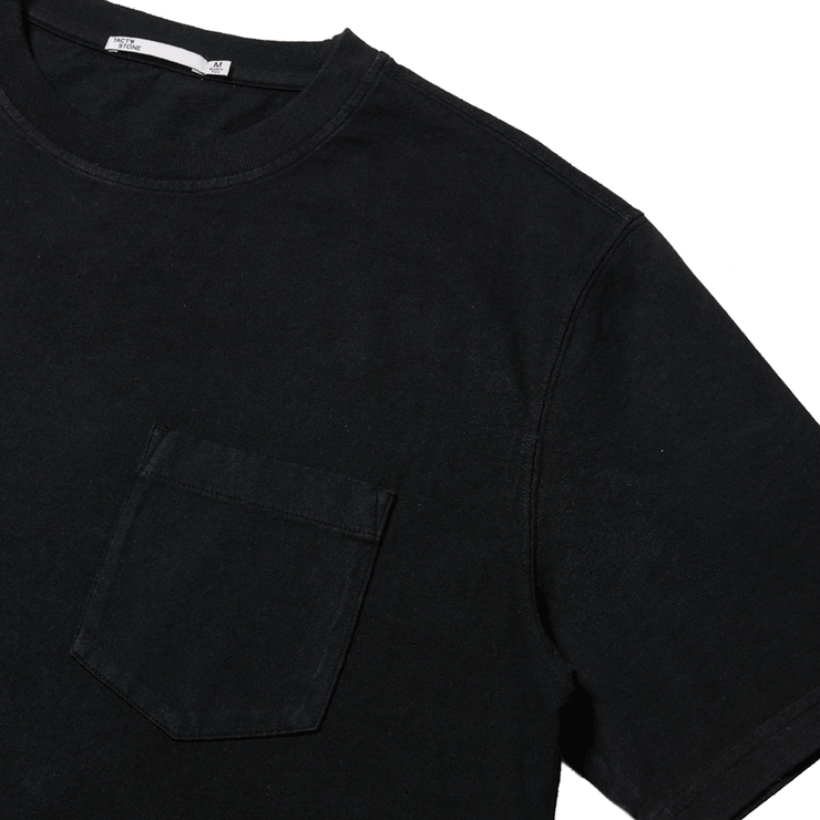 Flat lay focused on the left chest pocket of a short sleeve, black, pocket tee shirt.