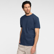 Model side facing wearing a navy, short sleeve, pocket tee shirt.