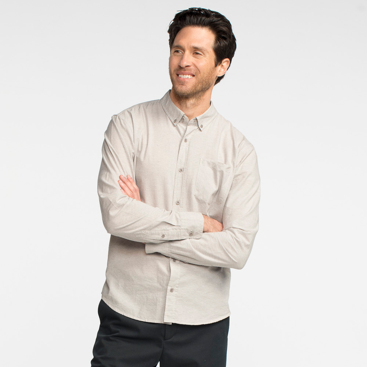Model front facing with his arms crossed, wearing a long sleeve, heather grey, button up shirt.
