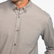 Zoomed in view of the top half of a heather grey, long sleeve, button up shirt, on a model.