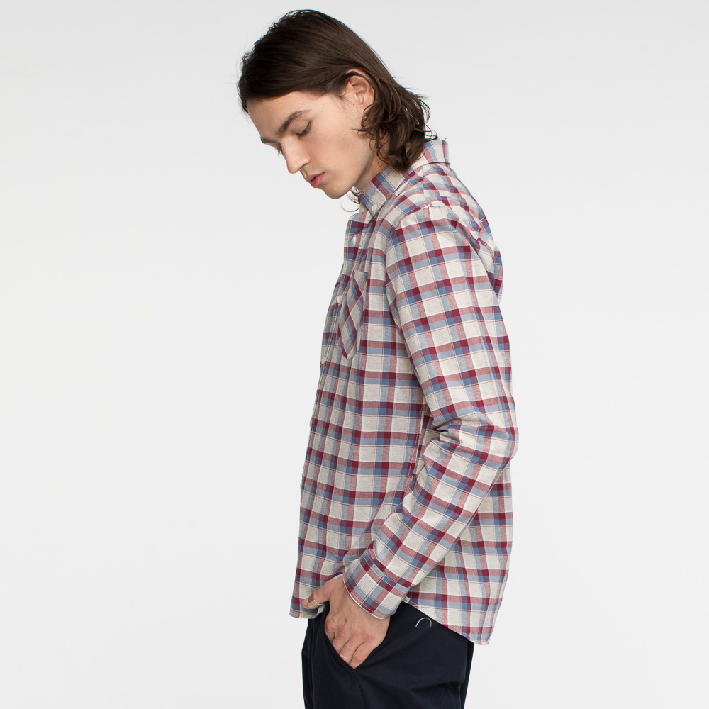 Model side facing wearing a long sleeve, plaid, button up shirt.