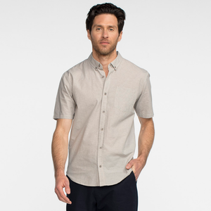 Model front facing wearing a short sleeve, heather grey, button up shirt.