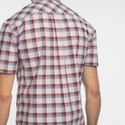 Model facing back wearing a short sleeve, plaid, button up shirt.
