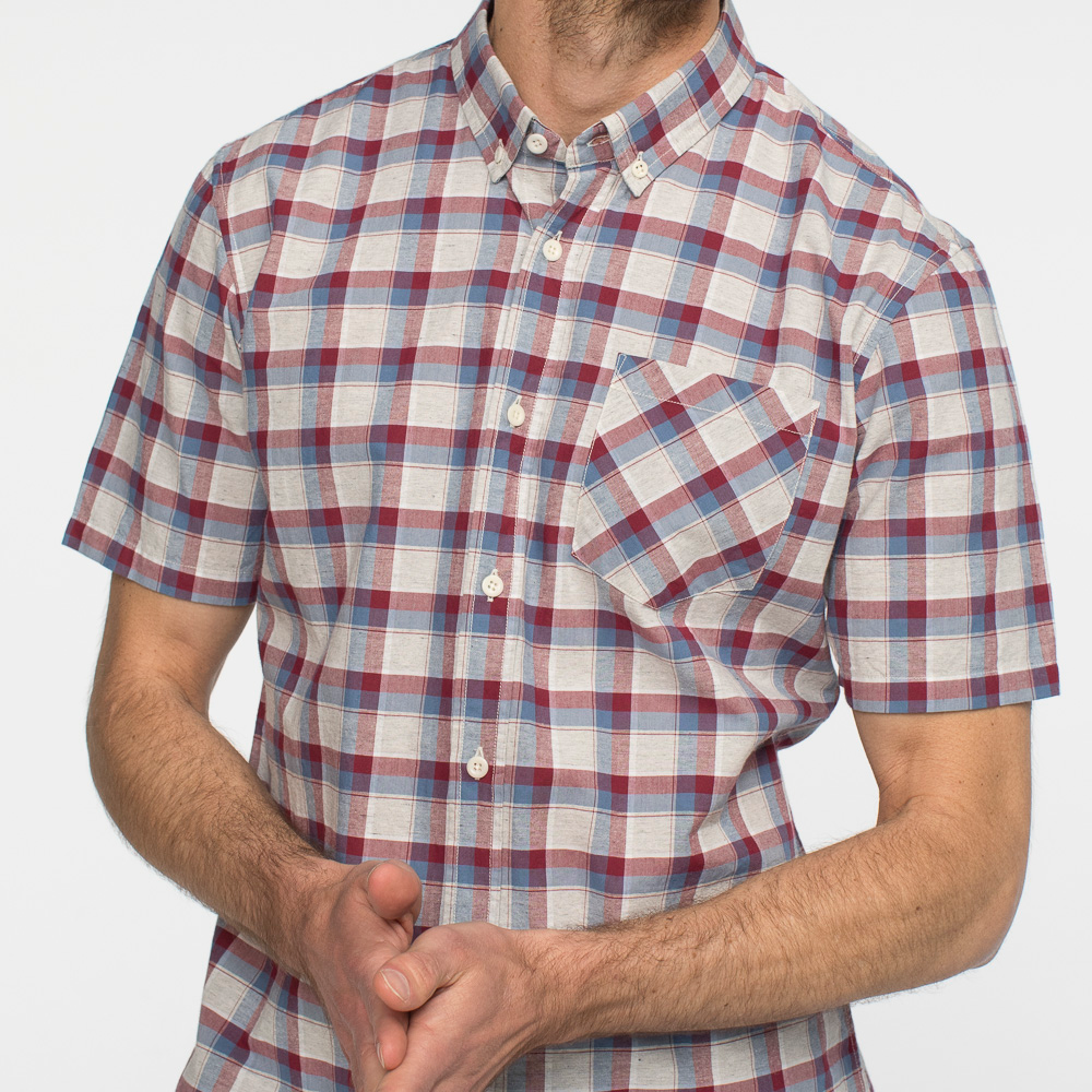 Zoomed in view of a short sleeve, plaid, button up shirt, on a model facing front.