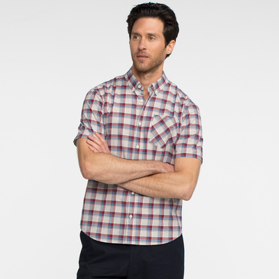 Model front facing with his arms crossed, wearing a short sleeve, plaid, button up shirt.