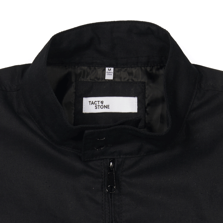 Zoomed in flat lay focusing on the collar of a zip up, black, blouson jacket. Focused on the Tact & Stone neck label, and button closure of the collar.