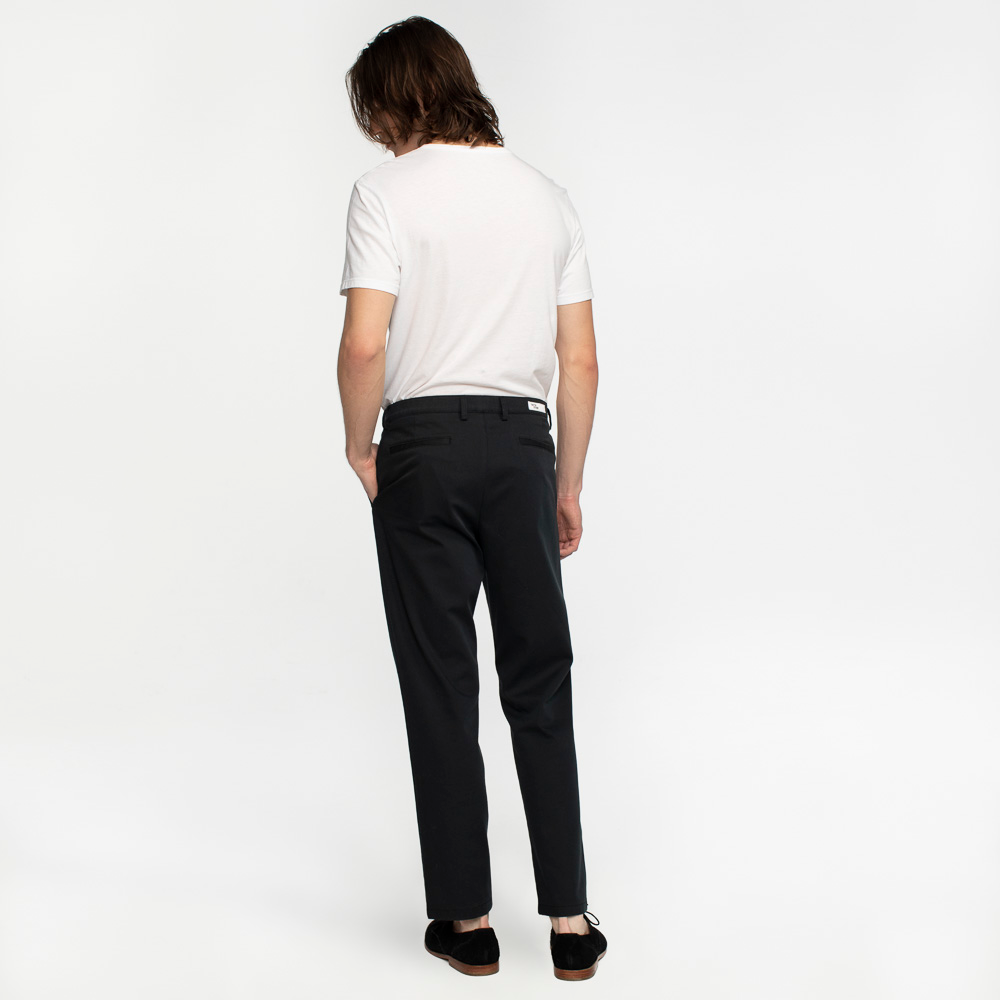 Model back view highlighting performance, sustainable black chinos.