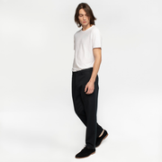Model side facing wearing black chinos.
