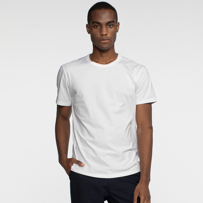 Model front facing wearing sustainable, performance white tee shirt. Organic cotton and recycled polyester white tee shirt.