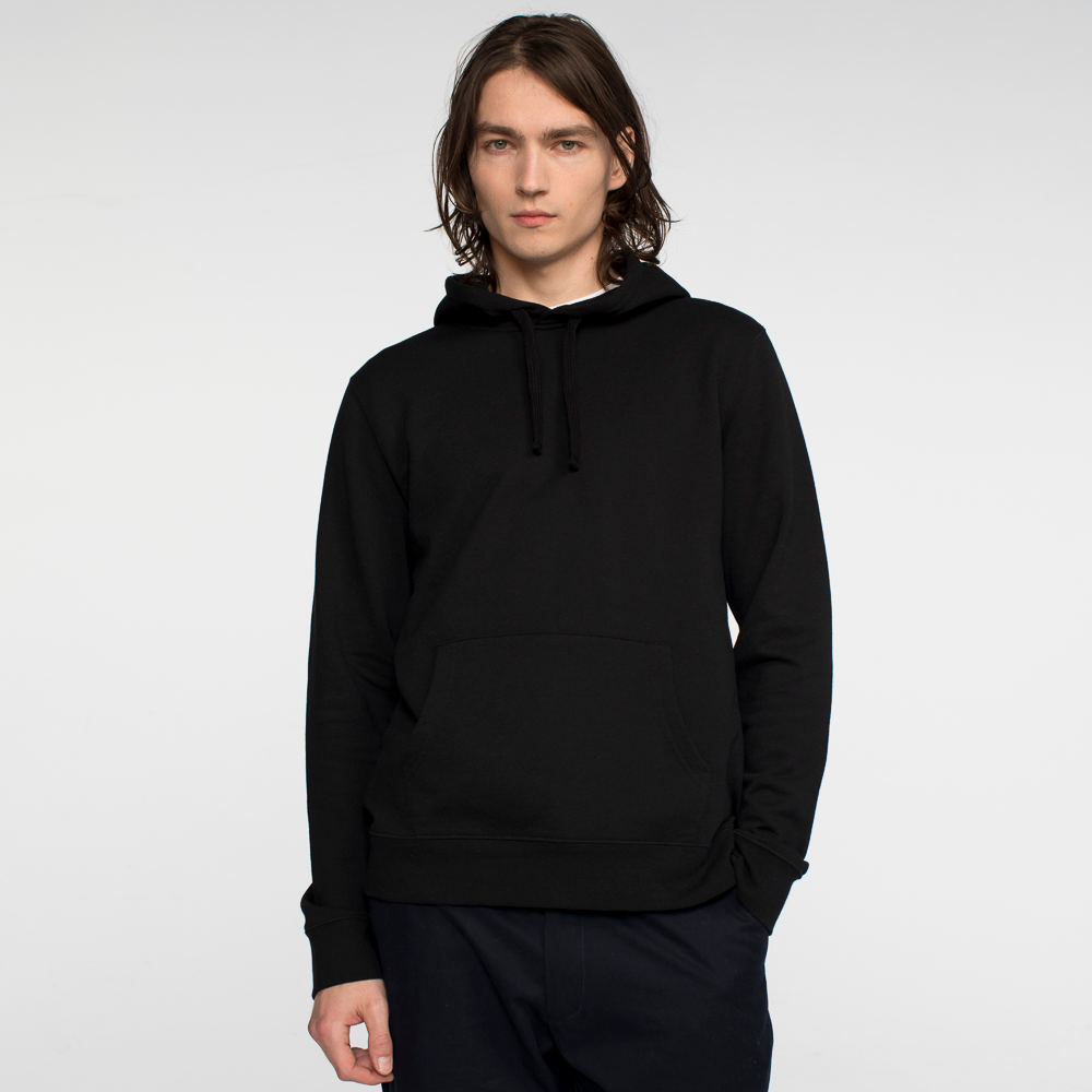 Model front facing wearing a black hooded sweatshirt.