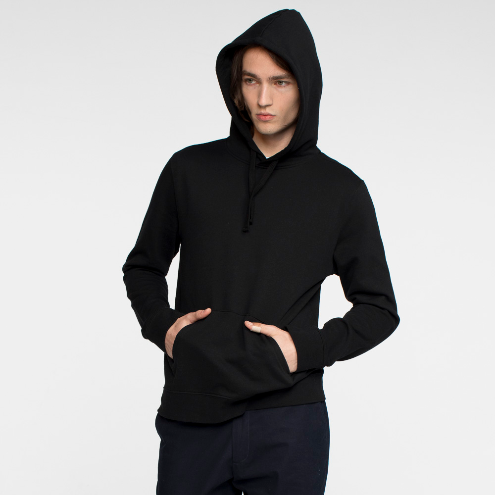 Model facing front with hands in front pouch pocket and hood over his head, wearing a black hooded sweatshirt.