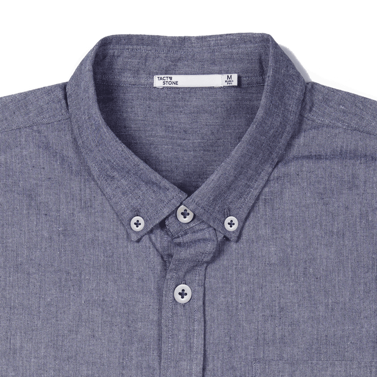 Zoomed in flat lay of the collar and buttons of a chambray button up shirt.