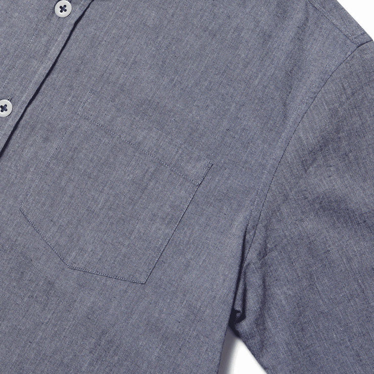 Zoomed in flat lay of left pocket of a long sleeve, chambray, button up shirt.