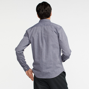 Model facing back wearing a long sleeve, chambray, button up shirt.