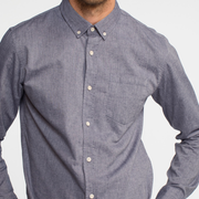 Zoomed in view on chambray, long sleeve, button up shirt on a model.