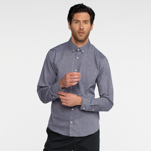 Model front facing wearing a long sleeve, chambray, button up shirt.