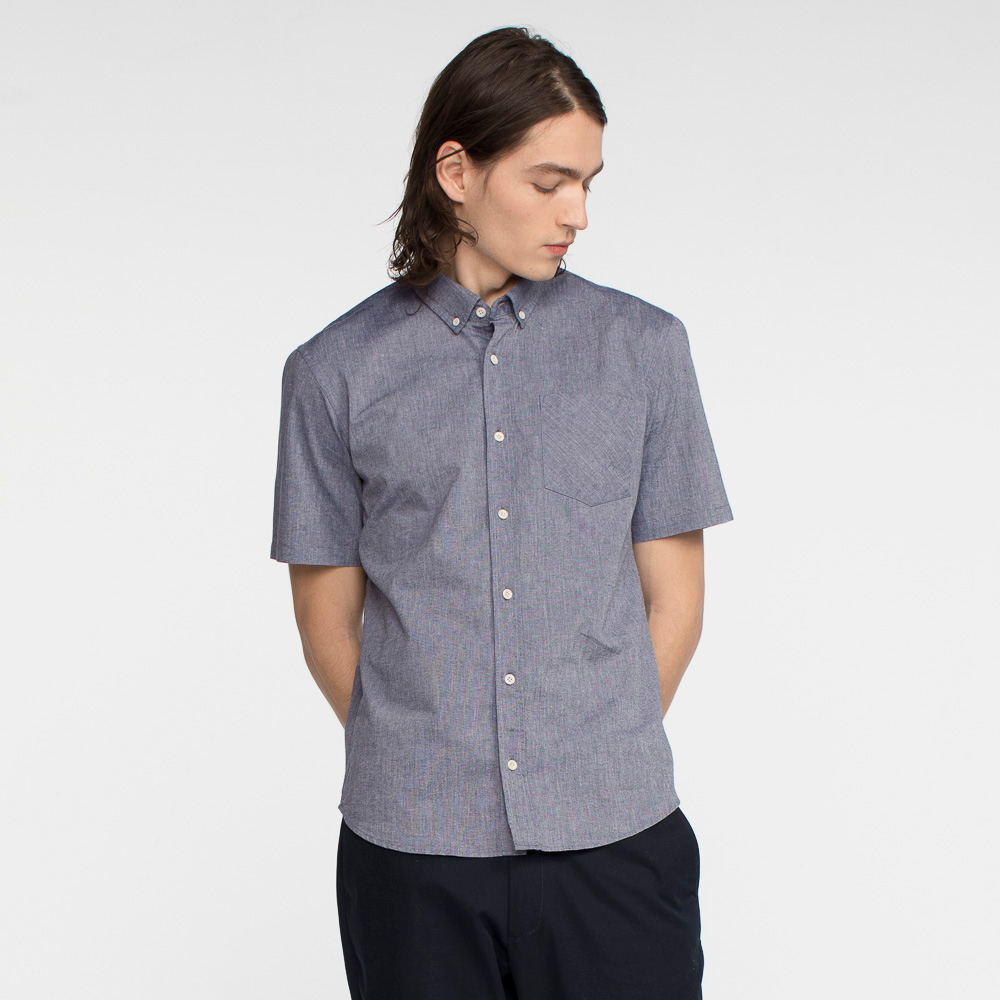 Model front facing with hands behind his back, wearing a short sleeve, chambray, button up shirt.